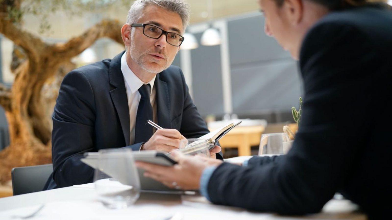 Två personer i kostym som diskuterar och antecknar vid ett bord