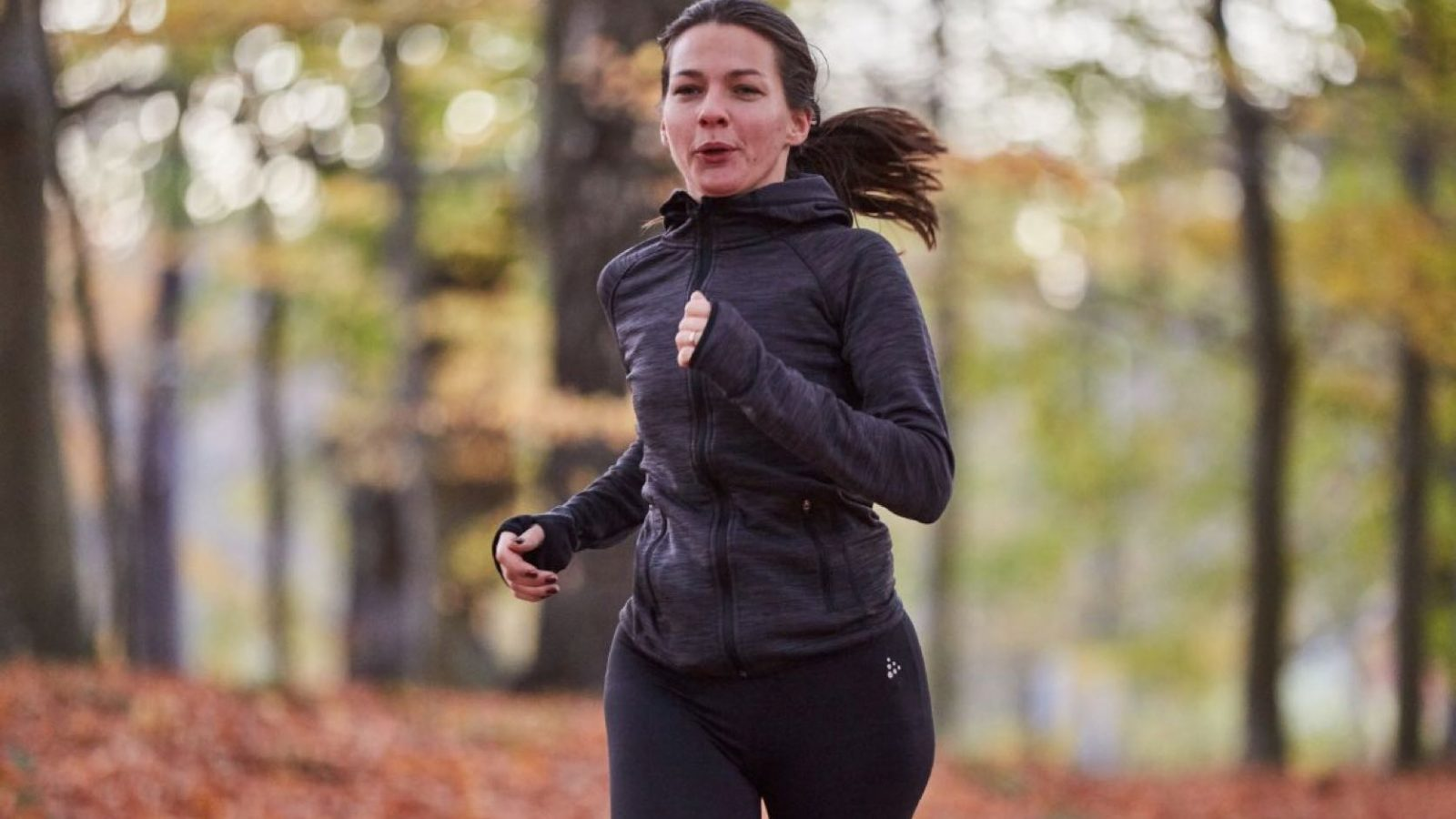 En tjej i gråa träningskläder som springer i skogen
