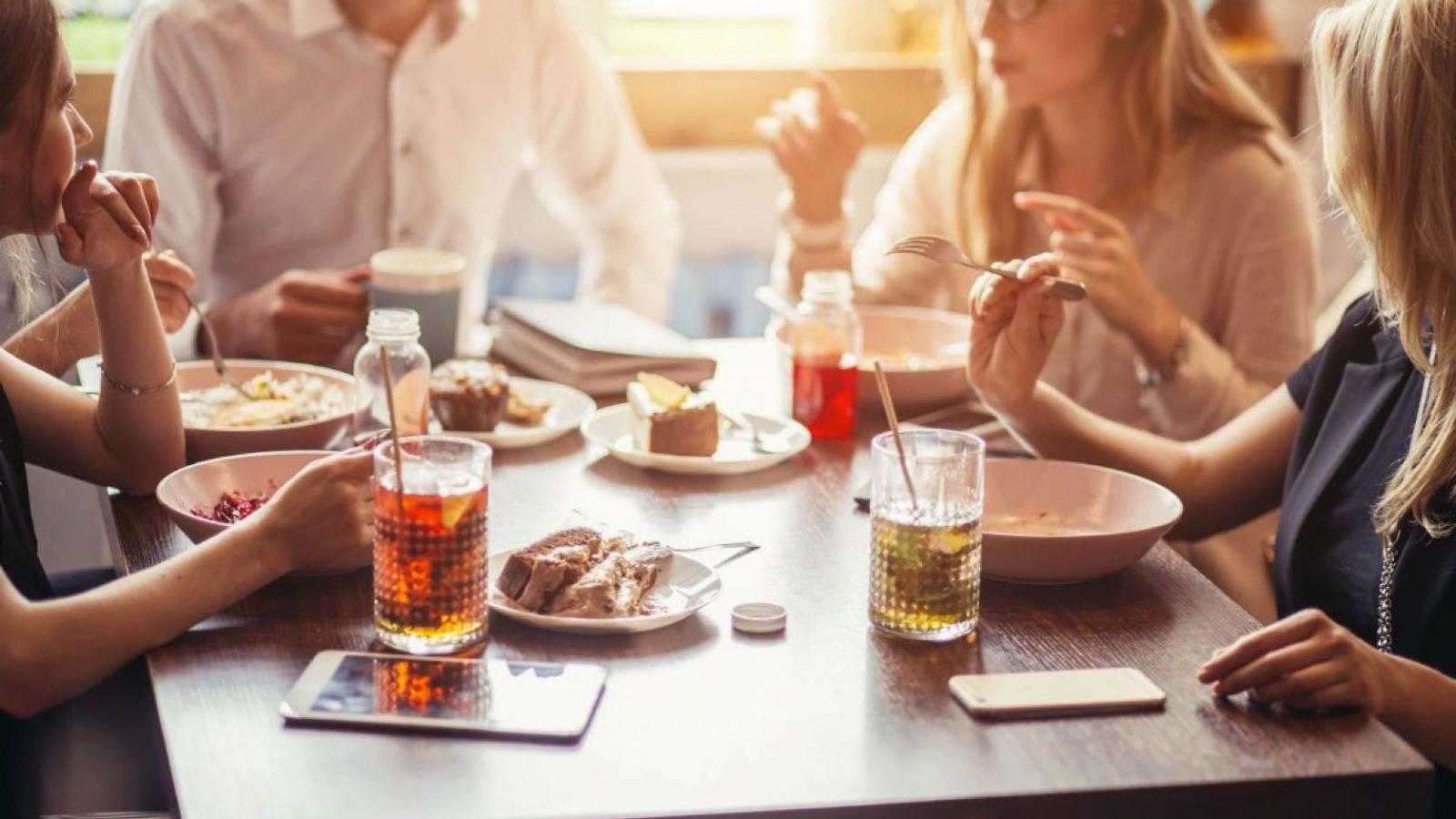 4 personer sitter och äter runt ett bord