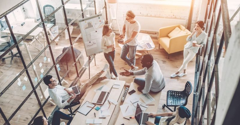 Bild tagen ovanifrån på ett kontor med 5 glada personer