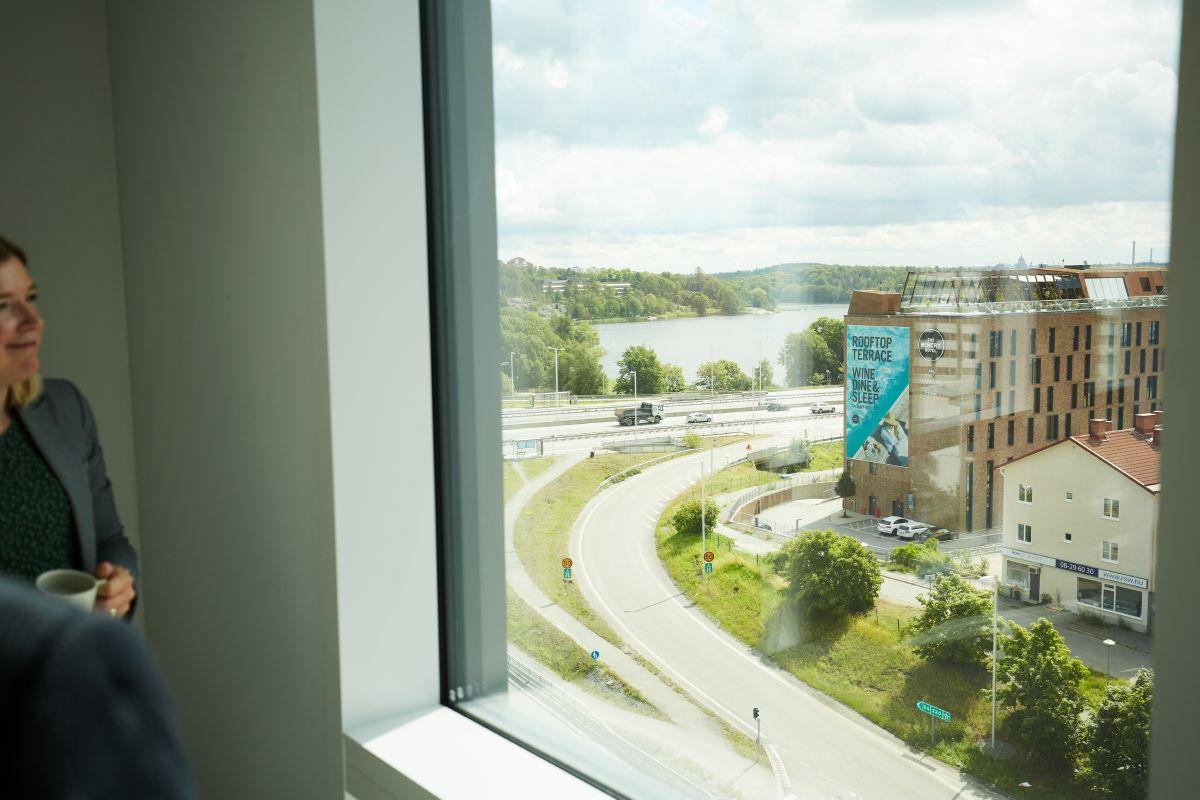 En kvinna tittar genom fönstret ut mot ett stadslandskap.